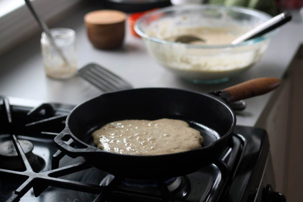 Delicious and nourishing rustic sourdough pancake cooking in the cast iron pan.