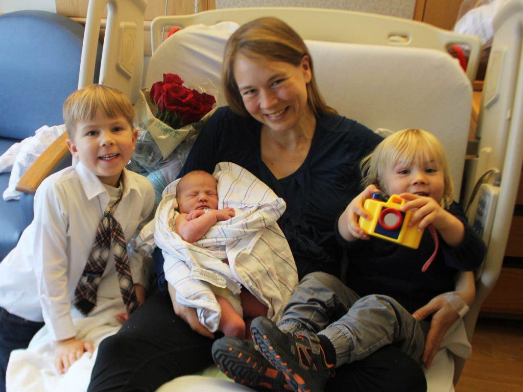 Mom with newborn baby and brothers.